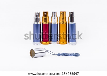 Metal perfume atomizers of the same cylindrical shape ranked. Cap with a brush in front of them. Isolated image on white background.