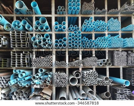 Metal pipe,Steel Angled Bar and PVC pipe stack on shelf - stock photo