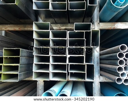 Metal pipes and pvc pipes stack on shelf - stock photo