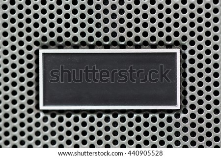 Metal plate label on metal steel grid with repetitive rows of punched circular holes, background and texture, Metal Grid for industrial.