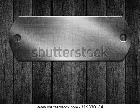 metal plate on a wooden background - stock photo