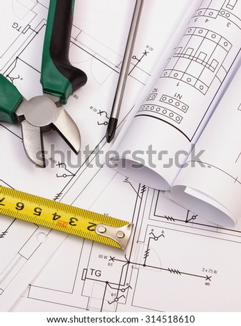 Metal pliers, screwdriver, tape measure and rolls of diagrams on electrical construction drawing of house, work tool and drawing for engineer jobs, concept of building house - stock photo