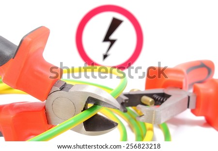 Metal pliers with green yellow electric cable and high voltage danger sign in background, pliers cut the cable. Isolated on white background - stock photo