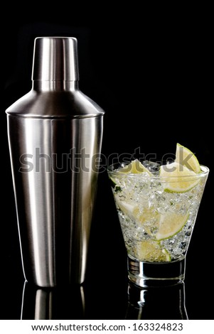 Metal polished shaker and sparkling cocktail with ice and  lime in old fashion glass on a black background