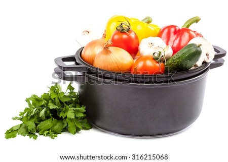 Metal pots and pans with vegetables isolated on white background. - stock photo
