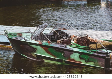Metal powerboat camouflage painting stand at the pier. Back view  - stock photo