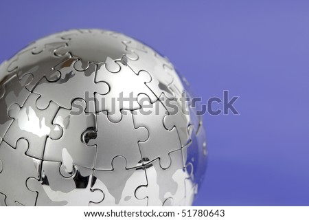 Metal puzzle globe isolated on white background, close-up on blue background