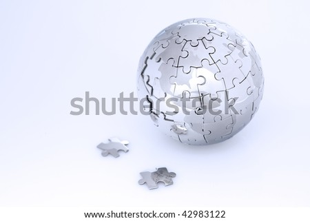 Metal puzzle globe isolated on white background, in blue light - stock photo