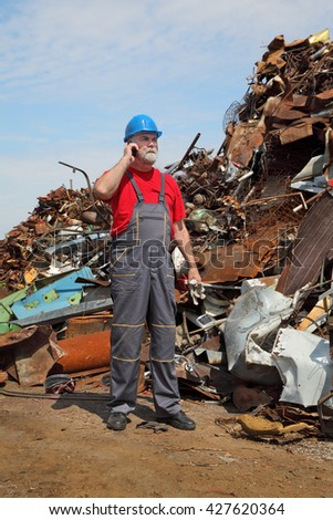 Metal recycling, worker speaking by mobile phone side by heap of scrap metal - stock photo