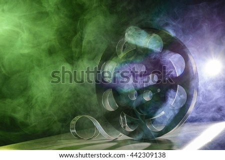 Metal reel of film is in the smoke at the table - stock photo