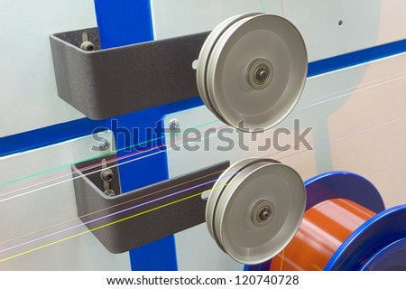Metal rollers with taut wire optical fiber - stock photo