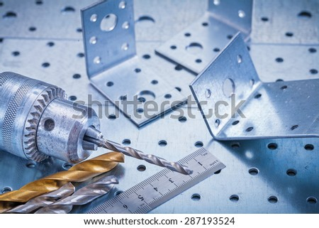Metal ruler drill boring bits and angle bars on perforated metallic background construction concept. - stock photo
