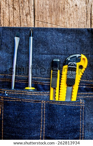 Metal Screw Driver with Stationery Knife Cutter Work Tools in Denim Tool Bag on Wood Table background / Concept and Idea of Industrial, Handmade, Home Improvement, Worker, Business or Art Crafts. - stock photo