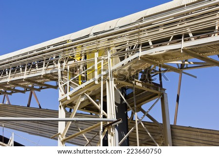 Metal sheets, railing, and piping, shade a walkway next to a cover conveyor belt.  - stock photo