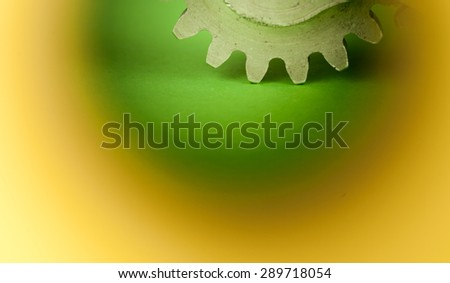 Metal shine cogwheel on green background observed through blurred hole in yellow planar piece of paper, symbolizing peeking and looking examining concept of mechanical machinery kinetic elements work - stock photo
