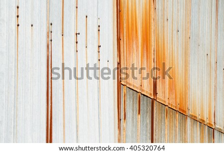 Metal siding overlapping with rust stains running down vertically from screws and rivets. - stock photo