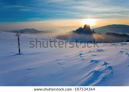 Metal signboard in snow on mountain in sunset - stock photo