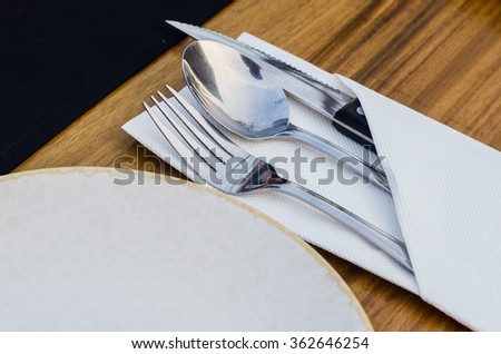 Metal silverware setting wrapped in cloth. - stock photo