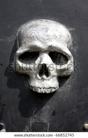 Metal skull door, fishing district of Genoa, Italy