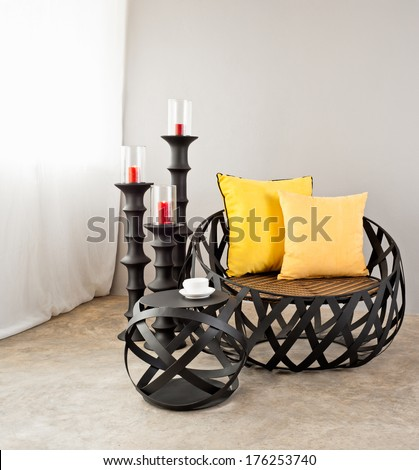 Metal sofa with yellow pillow and candles - stock photo