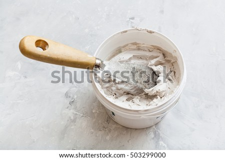 metal spatula with wooden handle in tube with putty on the concrete floor