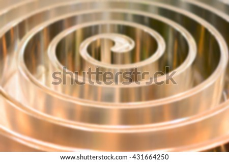 Metal spiral polished metal. Abstract background. Toning in the color golden metal. Deep blur.