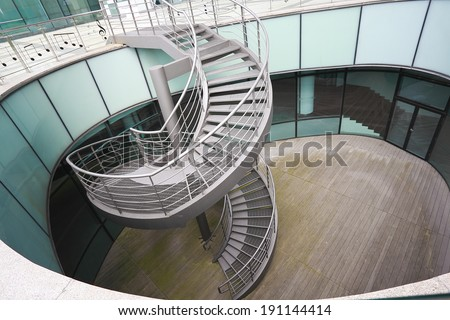 Metal spiral staircase at modern office building - stock photo