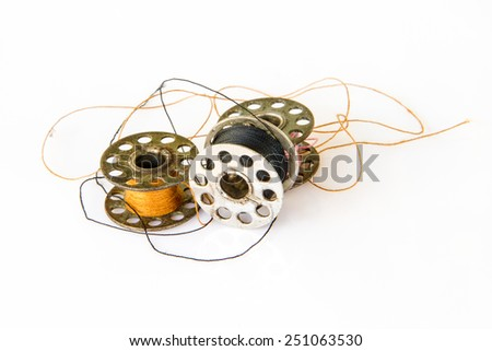 metal spool of thread or Sewing machine bobbins isolated on white - stock photo