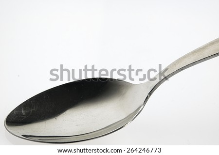 Metal spoon lying on the white kitchen table.