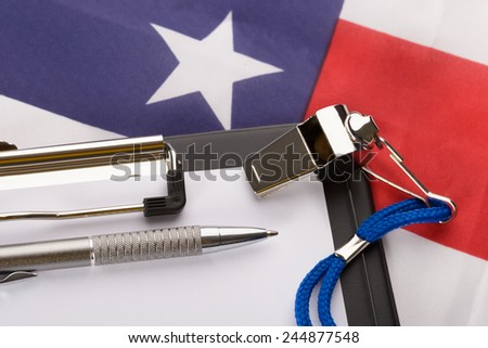 Metal Sport Whistle With Pen And Paper Sheet On American Flag - stock photo