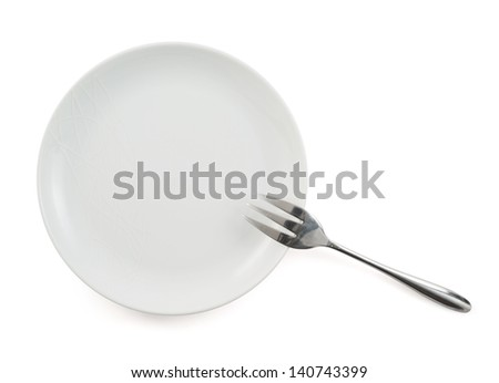 Metal stainless steel fork in a ceramic white plate isolated over white background, view above