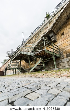 Metal staircase of an aged bridge on the cobble stone  paved street in Prague, Czech Republic