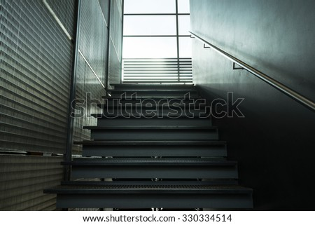 Metal stairs inside the building leading window - stock photo