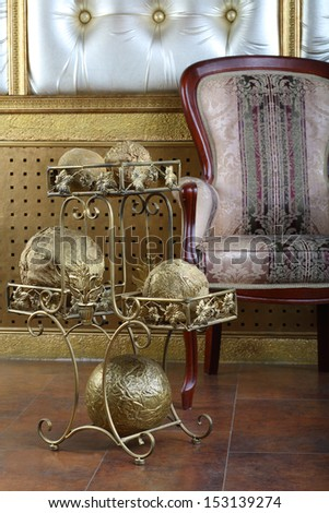 Metal stand with golden balls near chair in the interior of the studio