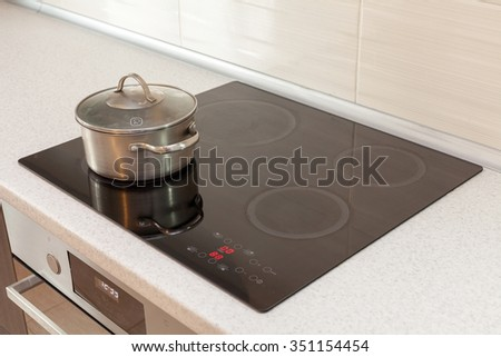 Metal steel saucepan in modern kitchen with induction stove - stock photo