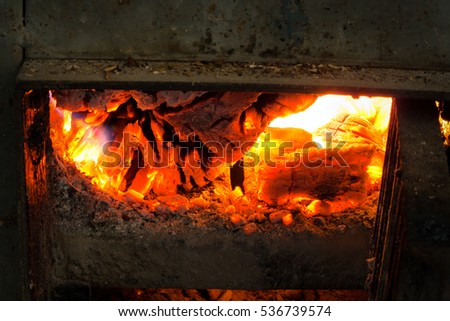 Metal stove with wood fire inferno inside