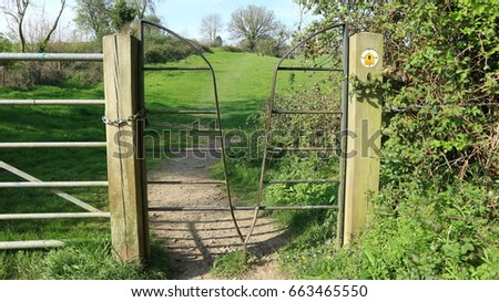 Metal stye on footpath through farmland in Cotswold Gloucestershire England
