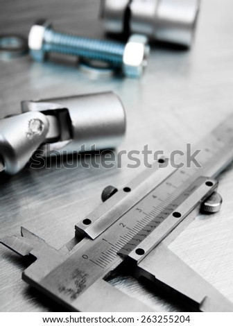 Metal style. �¡alliper and other metal tools on the scratched metal background.