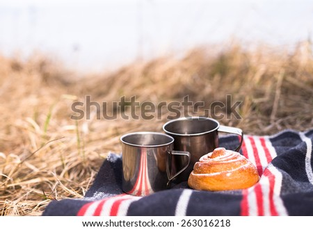Metal tea cups with bun in outdoor. Lifestyle and Hiking concept  - stock photo