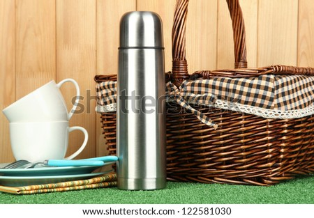 metal thermos with cups, plates and basket on grass on wooden background - stock photo