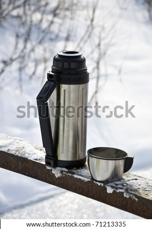 Metal thermos with hot tea drink. Winter. - stock photo