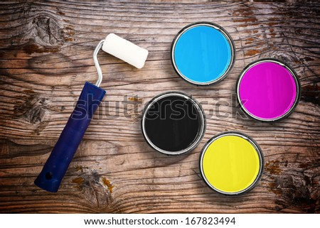 Metal tin cans with four process CMYK colors with paint roller. Printing industry conceptual background. - stock photo