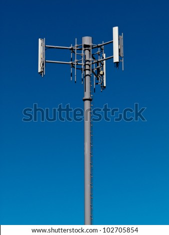 Metal tower with antennas for mobile cell phone telecommunications against blue sky with copyspace - stock photo