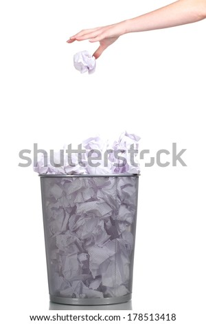 Metal trash bin from paper and hand isolated on white - stock photo