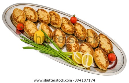 Metal tray with fish cakes decorated with lemon, tomato and green onions, on white background - stock photo
