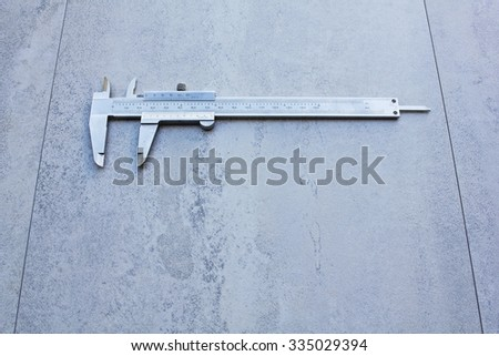 Metal vernier caliper isolated on tile surface background - stock photo