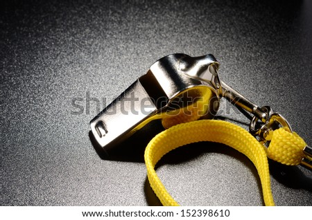 Metal whistle on a black grained surface - stock photo
