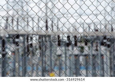 Metal wire fence or cage with High voltage electric power substation background - stock photo