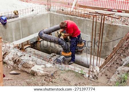 Metal worker is grinding weld on pipe junction completing a manhole for heating pipeline system. - stock photo