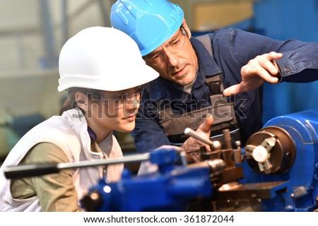 Metal worker teaching trainee on machine use - stock photo